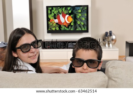 Two kids on couch watching TV with 3d glasses - a series of WATCHING TV images.
