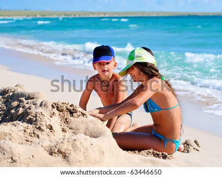 Two kids playing in sand at the beach