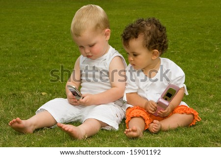 Two kids playing in the park with their parents' mobile phones