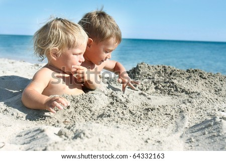 two kids playing on sand beach
