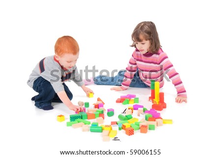 Two kids playing with colorful blocks. Isolated on white with shadows.