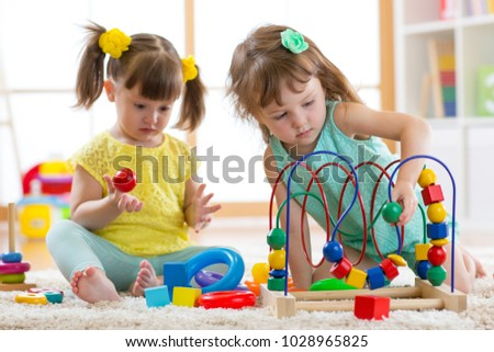 Two kids playing with wooden blocks in their nursery room #1028965825