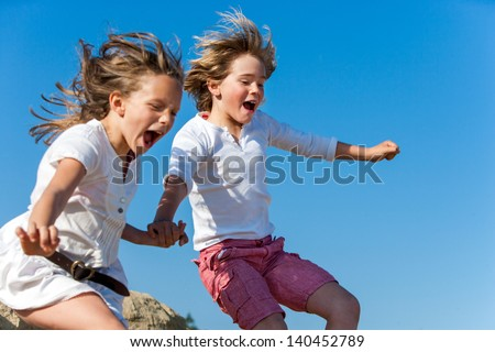 Two kids shouting and jumping together outdoors.