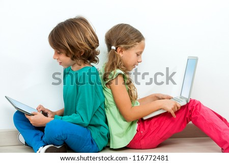 Two kids sitting back to back socializing with laptop and tablet.