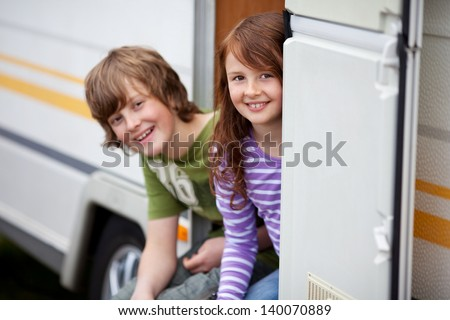 Two Kids Sitting In Doorway Of RV