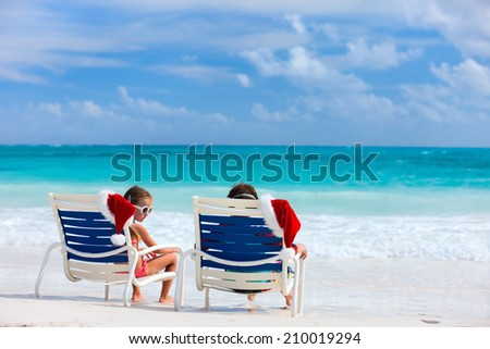 Two kids sitting on chairs with Santa hats at beautiful tropical beach enjoying Christmas vacation