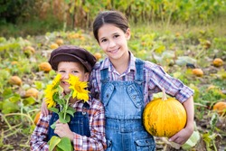 Two kids standing with pumpkin on vegetable garden