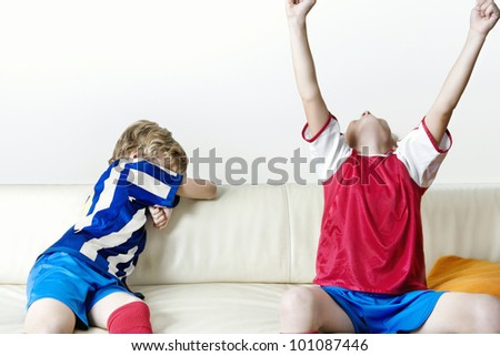 Two kids supporting different teams watching football and celebrating at home.