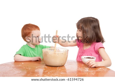 Two kids talking while baking cake. Isolated on white.