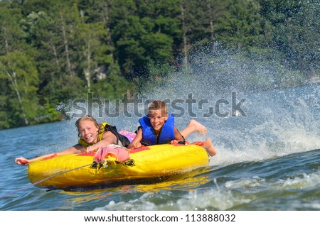 two kids trying not to fall off a water tube