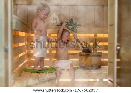 Two kids with a bucket and a basin in the sauna. Twin boys relax in the bath. Сute children in the sauna on a wooden shelf. Steam and heat in the Russian sauna Photo stock ©
