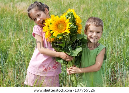 Two kids with bunch of sunflowers  in a wheat field