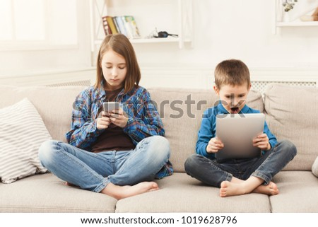 Two kids with gadgets. Sister and brother surfing the net or playing online games on smartphone and digital tablet at home. Modern communication and gadget addiction concept