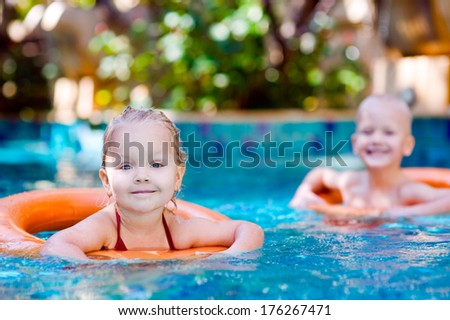 Two kids with lifebuoy in swimming pool