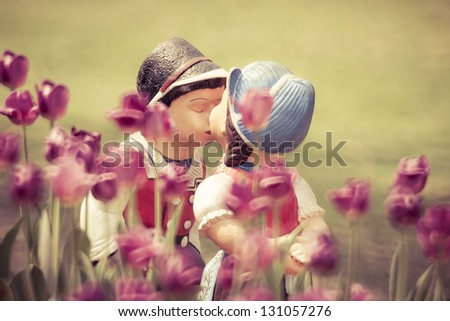 Two kissing vintage style dolls in tulip garden.