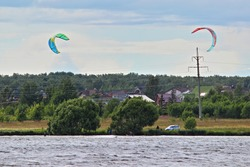 Two kite surfers in blue sky on river on Sunny summer day, kitesurfing extreme active recreation