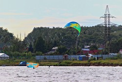 Two kite surfers near electric air power line wires on river on Sunny summer day, kiteboarding extreme active recreation safety