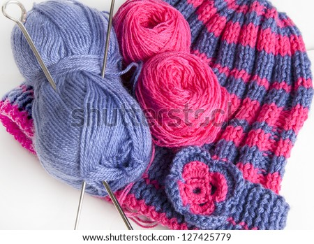 Two knitting needles, woolen yarn (worsted) clew and knitting cap