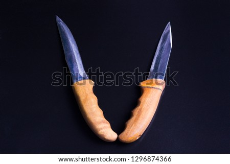 two knives with wooden handles lie the handle to the handle, on a black background