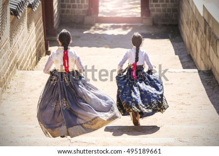 Two Korean Girls dressed in traditional dress running down stairs in Seoul street