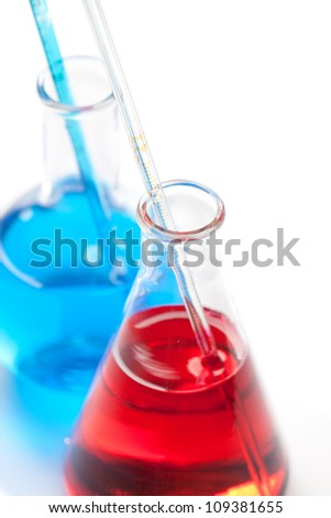 Two laboratory flasks - Clear liquid mixed with a colored chemical reagent, close-up view