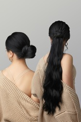 Two ladies are showing difference in hairstyle with and without black pony tail. Girls in the same beige cardigan and top are faced away. Lustrous strands for hair extension match girls' hair color.