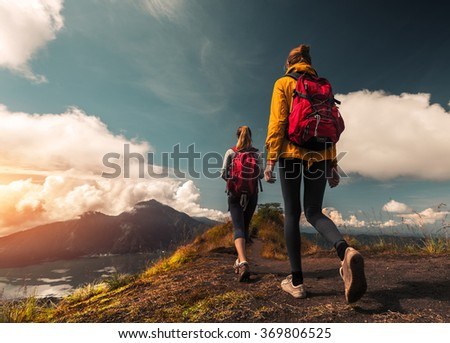 Two ladies hikers walking on the path on top of the mountain