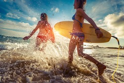 Two ladies running into the sea with surf boards