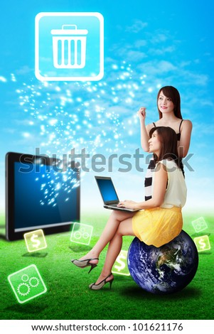 Two lady look at the bin icon from tablet computer on the grass field : Elements of this image furnished by NASA