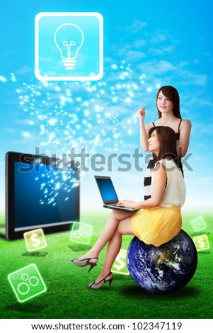 Two lady look at the Light bulb icon from tablet computer : Elements of this image furnished by NASA