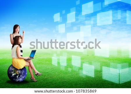 Two lady on grass field and hold notebook computer : Elements of this image furnished by NASA - stock photo
