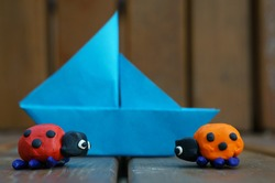 Two ladybugs made of plasticine on a wooden bench. In the background, a paper boat.