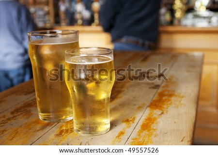 Two lager beers on a wooden table in a pub in daytime