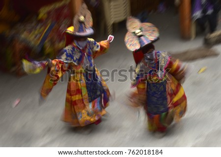 Two lamas in traditional bright sacred clothes and wide headdresses perform the dance Black Hats at the monastic festival. Monks photographed in the dynamics of movement. #762018184