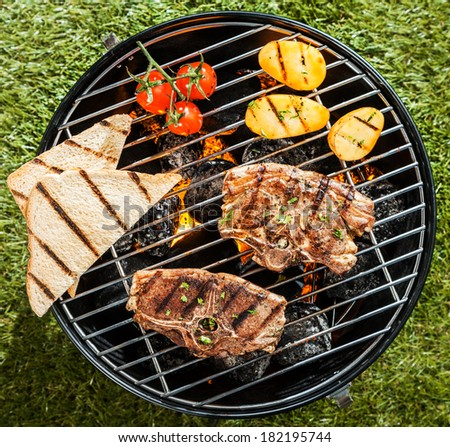 Two lamb chops cooking on a BBQ on a portable grill with tomato, potatoes and slices of toast on a sunny summer day outdoors on the grass, overhead view