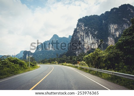 Two-lane road surrounded with mountains and forest in Khao Lak, Thailand