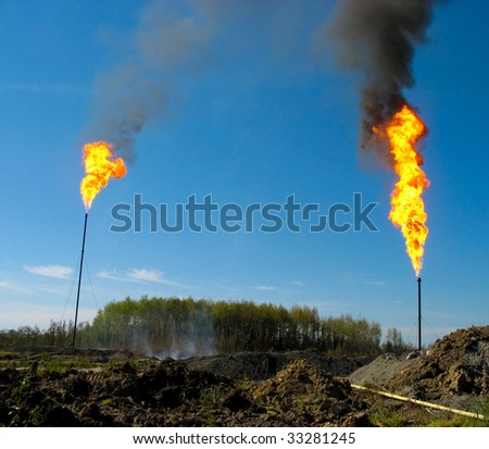 Two large and smoking oil flares