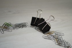 Two large black paper clips and small metal paper clips on a light wooden surface