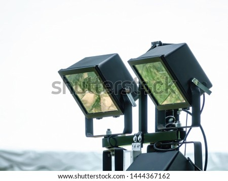 Two large gelled floodlights on swivel mounts for evening and nighttime illumination of garden events, with digital oil-painting effect, for industrial and entertainment motifs #1444367162