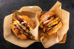 Two large grilled chicken burgers in a craft box on a dark background, top view. Takeaway hamburger. Burger in the box, fast food.