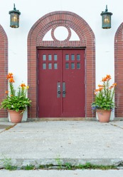Two large red, double doors with six small windows and a round metal door handle in each door. The exterior of the building has white stucco with vintage brass lanterns and two clay flower pots.