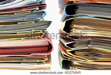 Two large stacks of colorful binders with white background - stock photo