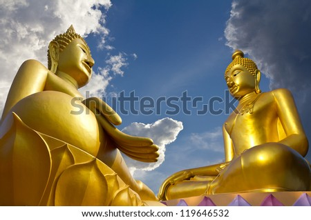 Two large statues of Buddha pagoda concentrate on clouds and sky.