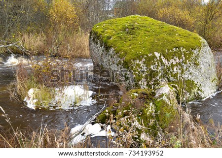 Two large stones in the forest, overgrown with age-old moss, lie in a creek and around them runs a boiling water