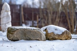 Two large stones lie on the snow and are illuminated by the warm spring sun against the background of a suburban area.