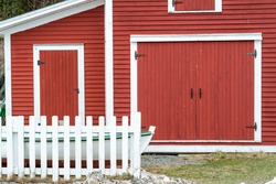 Two large vintage red wooden garage or barn doors with white trim.  The wood doors are closed and have two hinges on both sides. There's a bow of a wooden fishing boat in front of the doors.