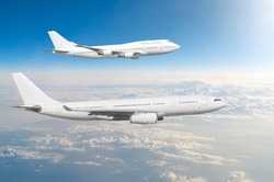 Two large white passenger airplanes fly parallel to each other in the sky above the clouds