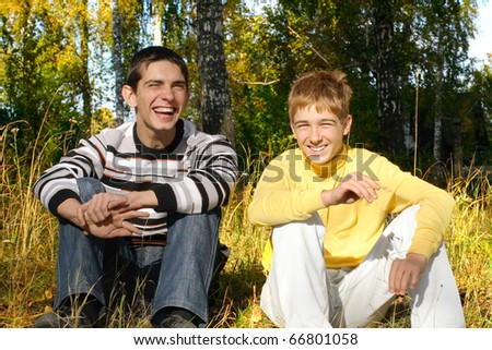 two laughing boys sitting in autumn forest