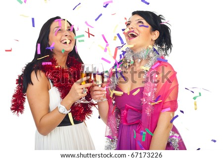 Two laughing women at party celebrating with champagne and confetti