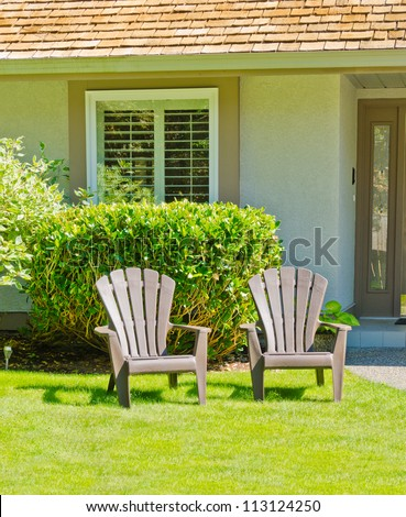 Two lawn chairs at the front ( back ) yard.